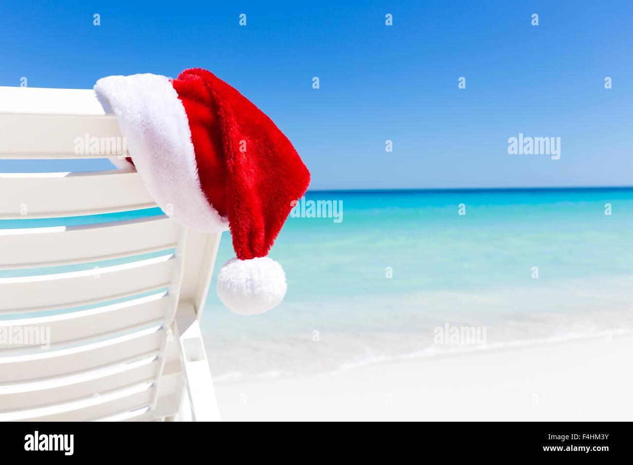 Santa Claus Hat on sunbed near sandy beach with turquoise caribbean ...