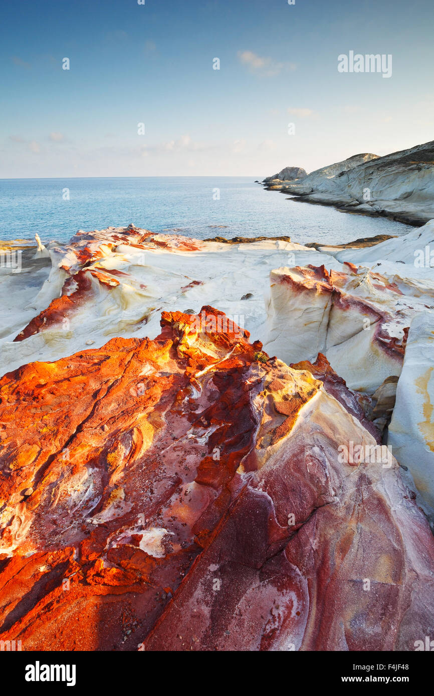 Coast nearby Mandrakia village in the north of Milos island lit by morning light. - Stock Image