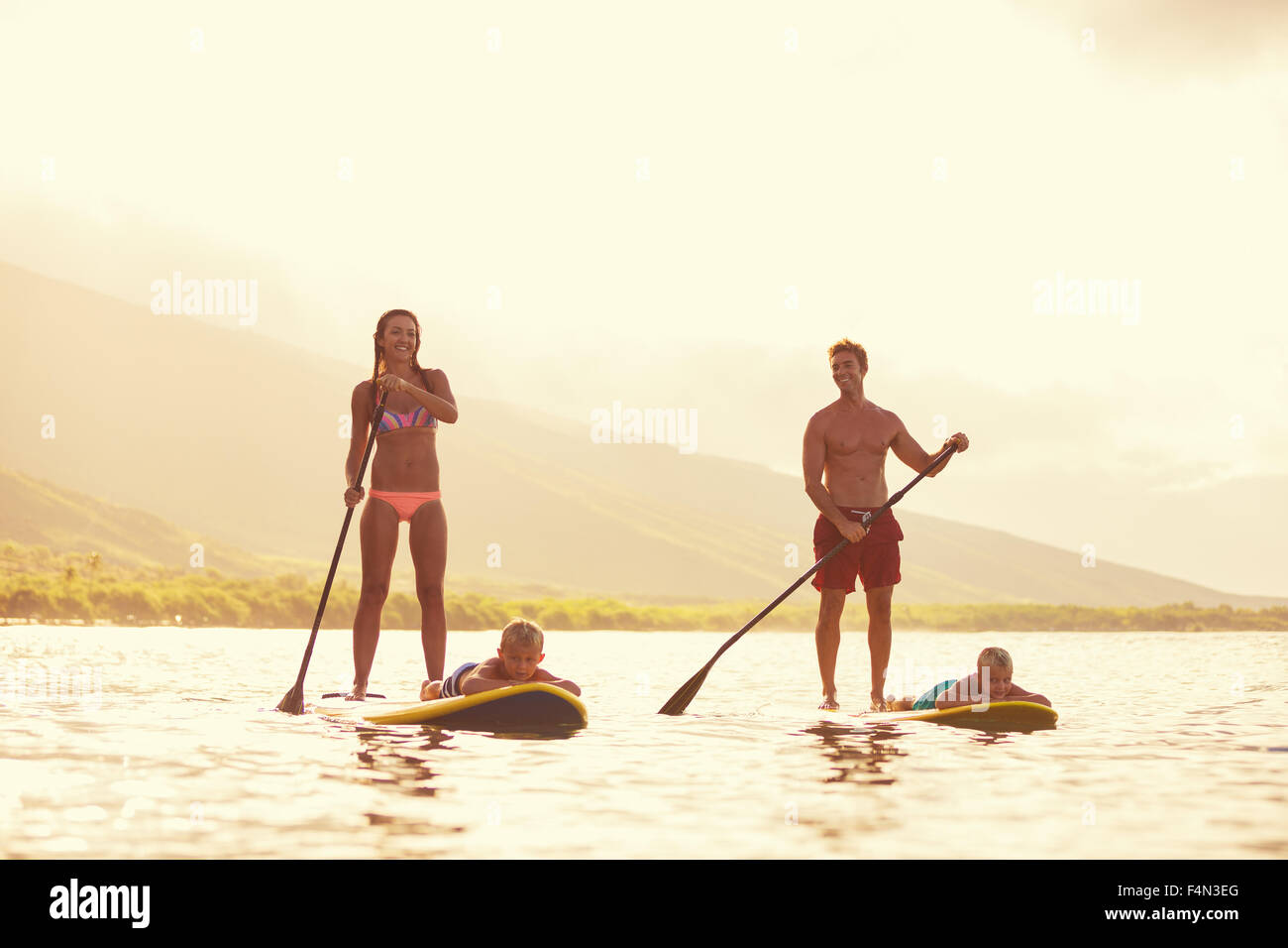 Family stand up paddling at sunrise, Summer fun outdoor lifestyle - Stock Image
