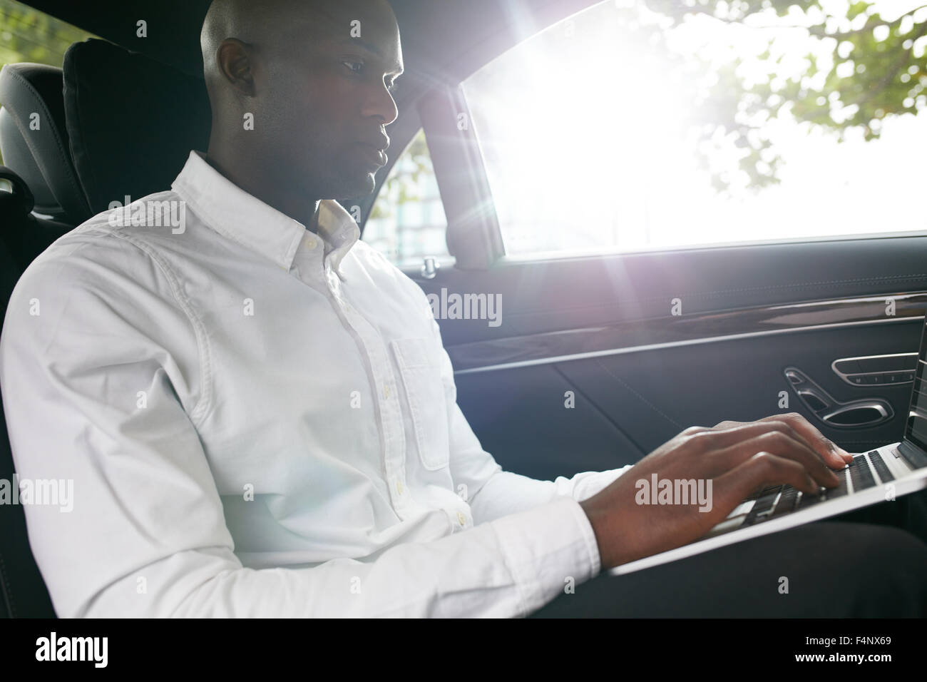 Businessman traveling to office in the luxury car on the back seat and working on the laptop. - Stock Image