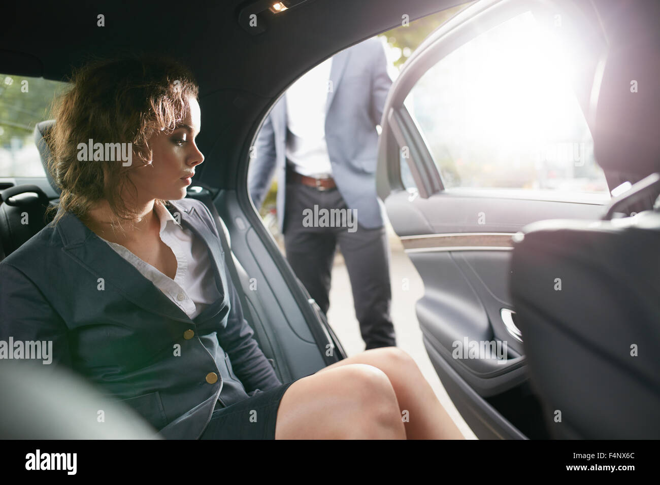 Man opening a passenger door for a businesswoman getting out of a car. Female entrepreneur traveling to office in - Stock Image
