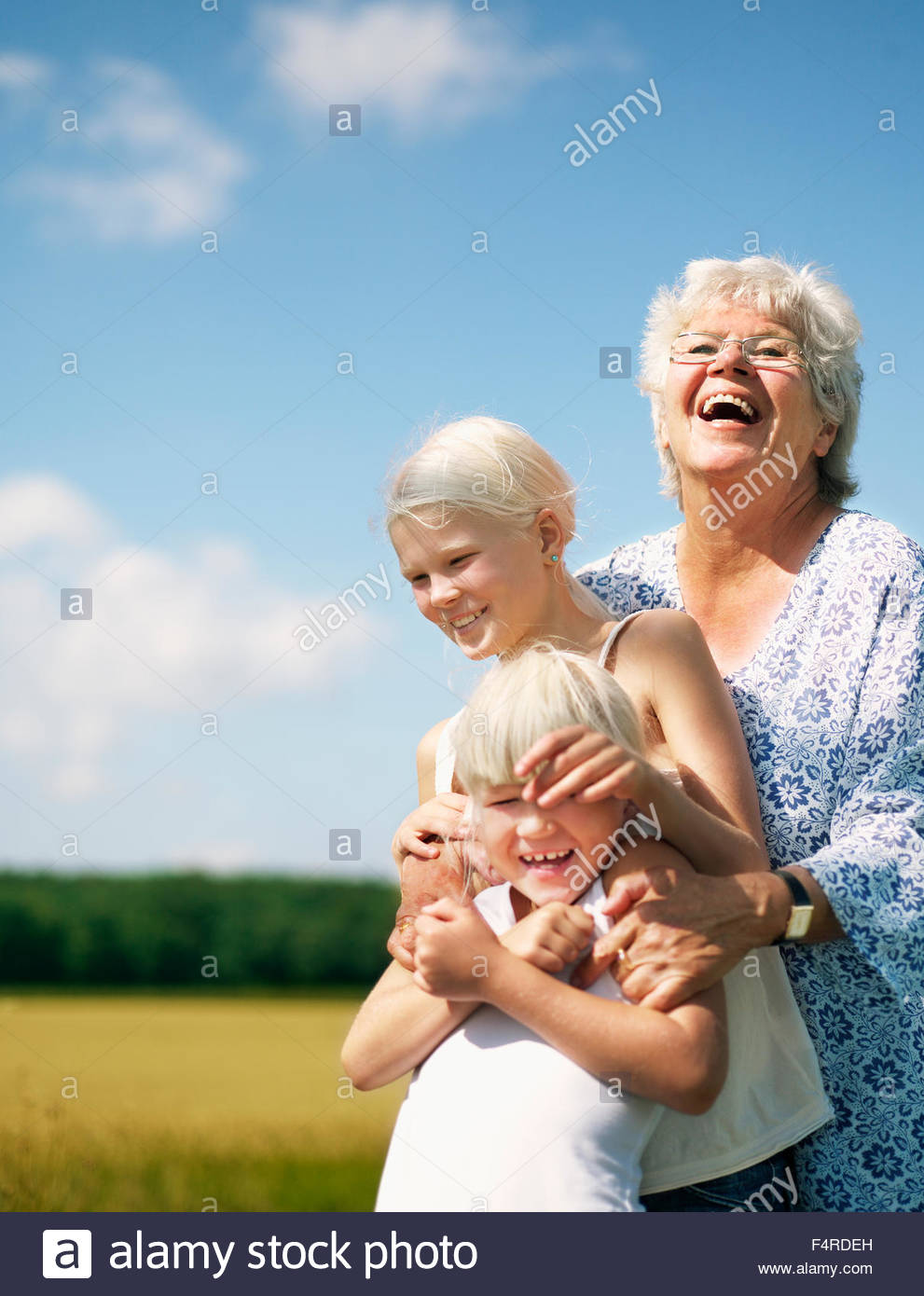 Outdoor portrait of grandmother with two granddaughters (6-7, 12-13) - Stock Image