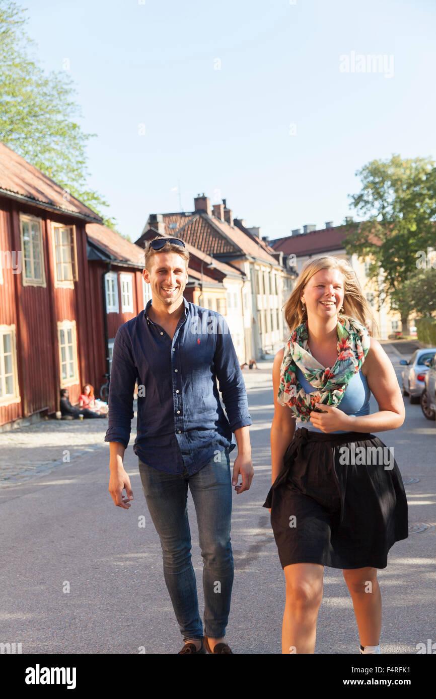 Sweden, Sodermanland, Sodermalm, Stockholm, Cheerful couple walking along street - Stock Image