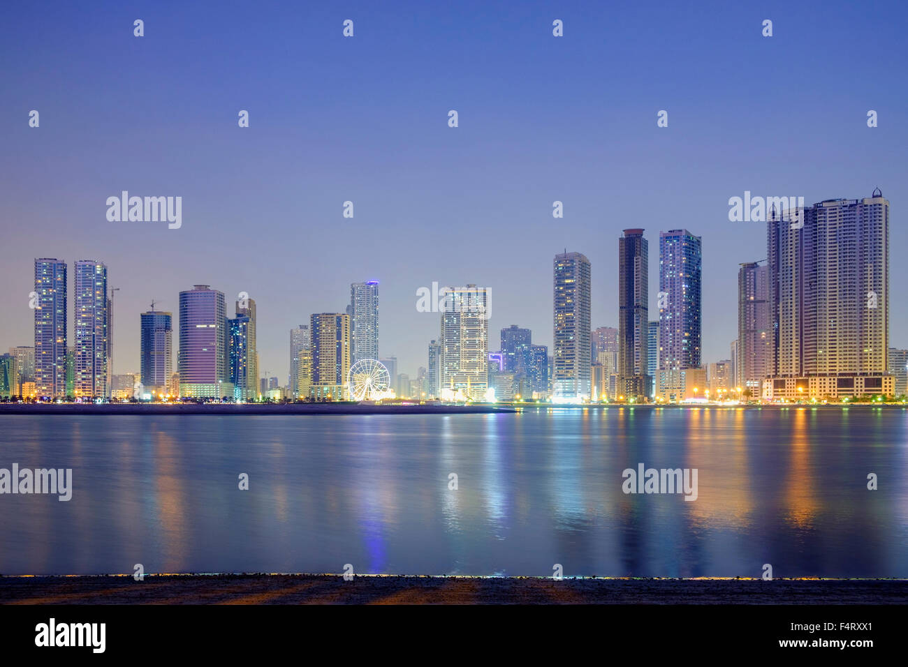 Night skyline view of modern high-rise apartment buildings along Corniche in Sharjah United Arab Emirates - Stock Image