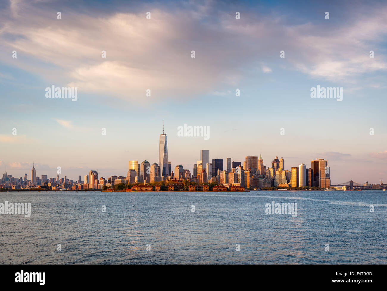 New York skyscrapers and Lower Manhattan's Financial District in sunset light with Battery Park and Ellis Island. - Stock Image