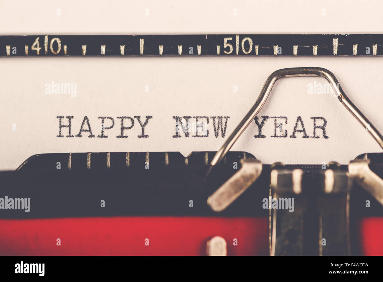 Happy New Year on old typewriter machine, hipster lifestyle holiday letter and greeting card, retro toned, selective - Stock Image