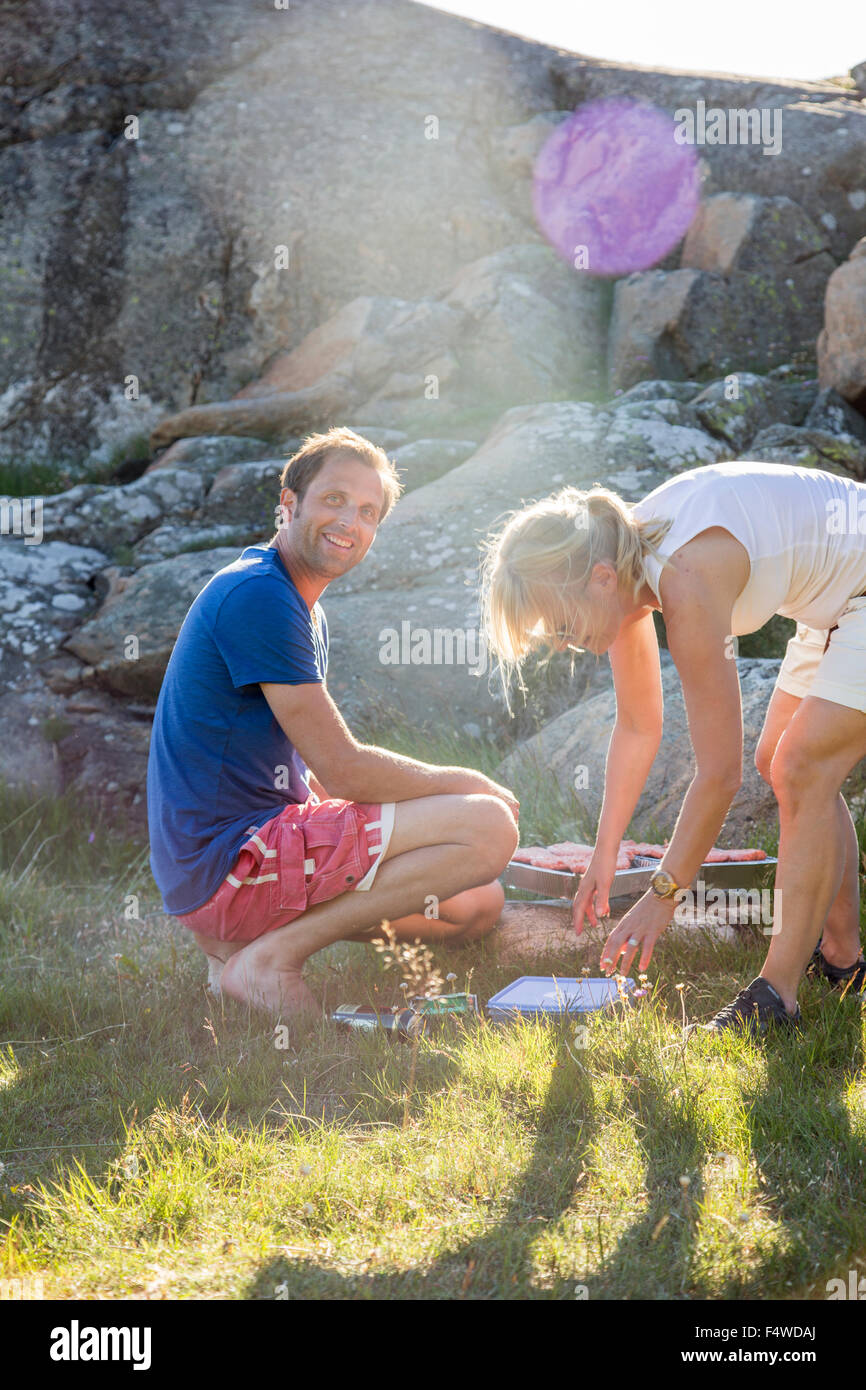 Sweden, Swedish West Coast, Halland, Kungsbackafjorden, Couple cooking food on barbecue grill - Stock Image