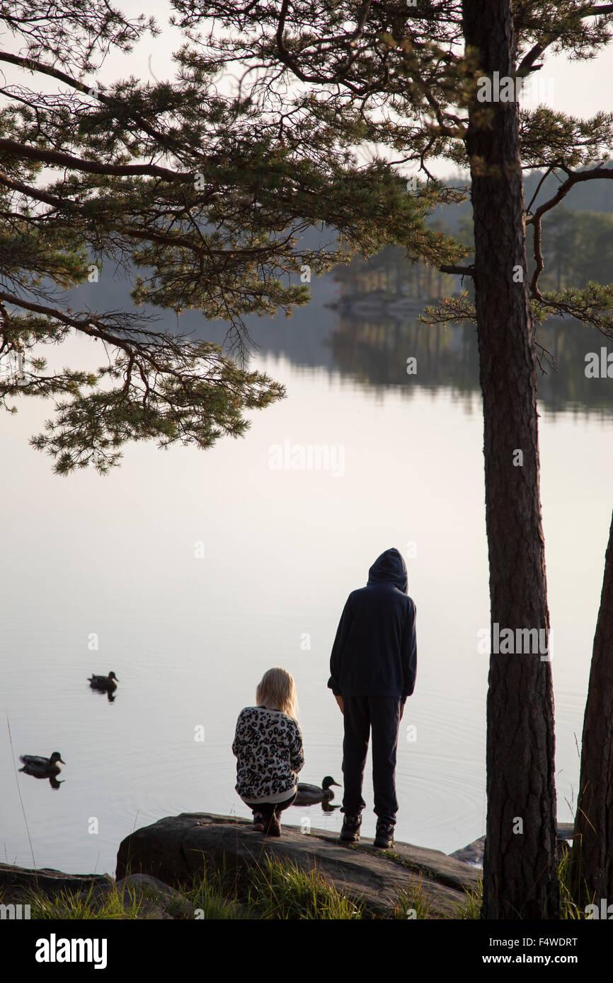 Sweden, Vastergotland, Harskogen, Stora Harsjon, Boy (12-13) and girl (10-11) by lake - Stock Image