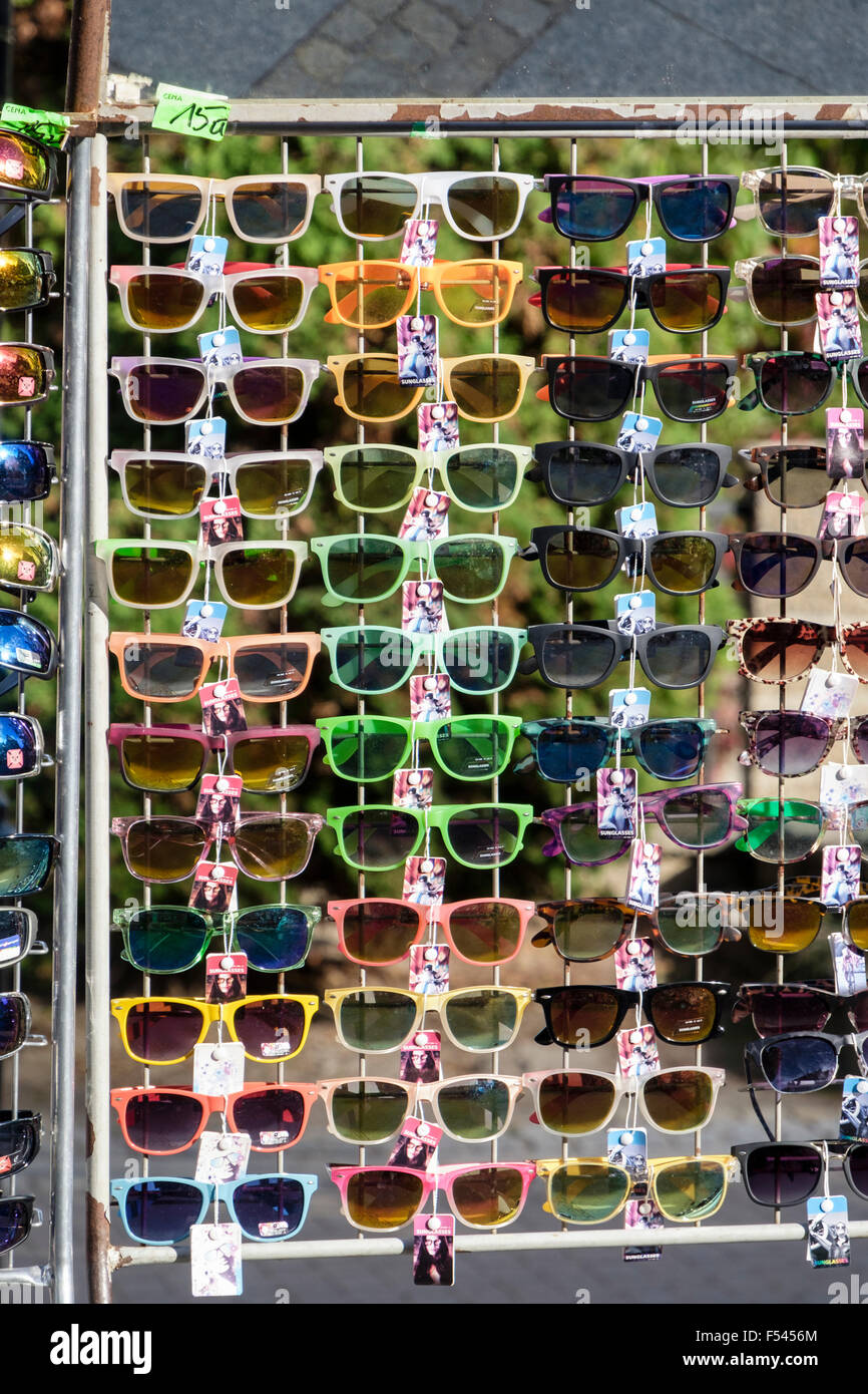 Lots of new pairs sunglasses with coloured frames for sale on a rack ...