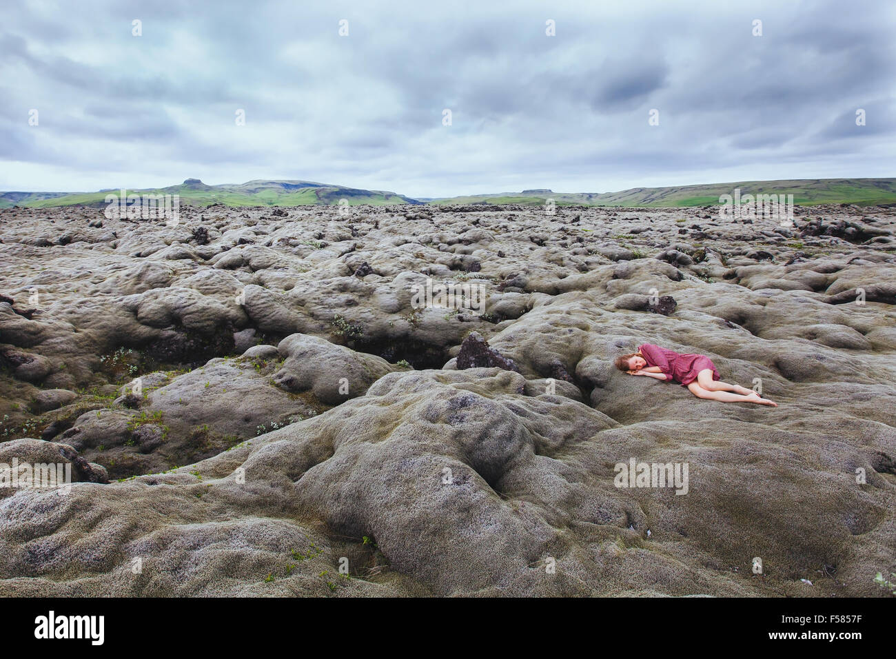 beautiful girl in red dress sleeping in lava field in Iceland, solitude concept - Stock Image