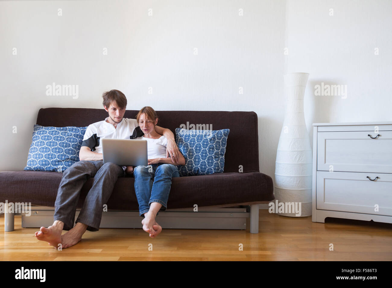 young family using laptop at home, couple on the couch with computer - Stock Image