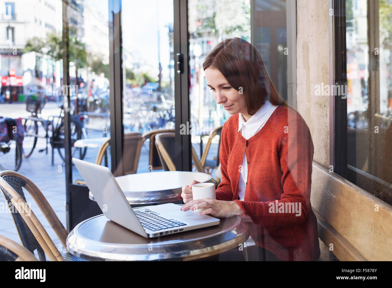 young woman working with laptop in cafe - Stock Image