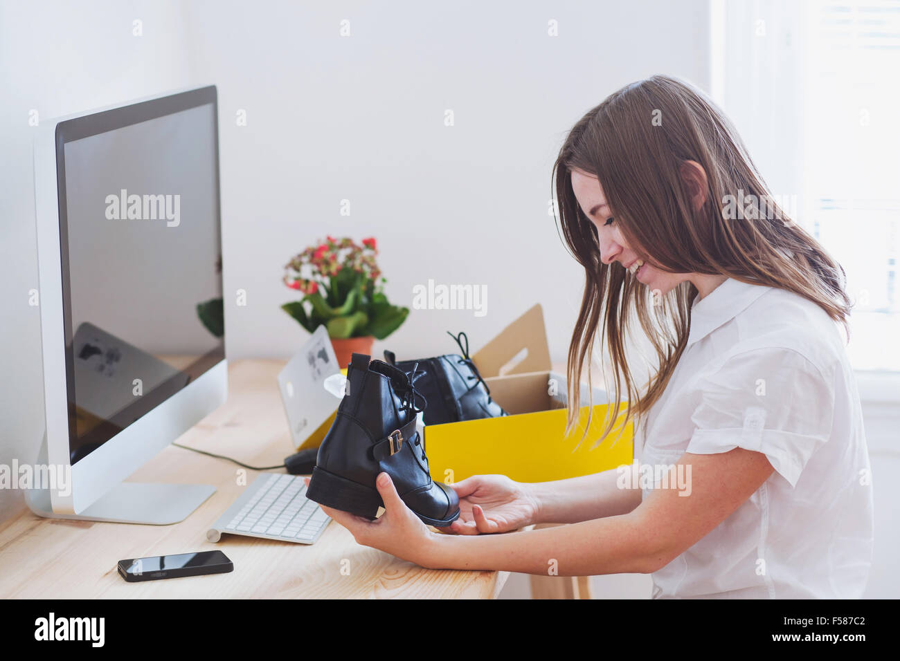 shopping online concept, happy woman opens box with new shoes, ordered by internet - Stock Image