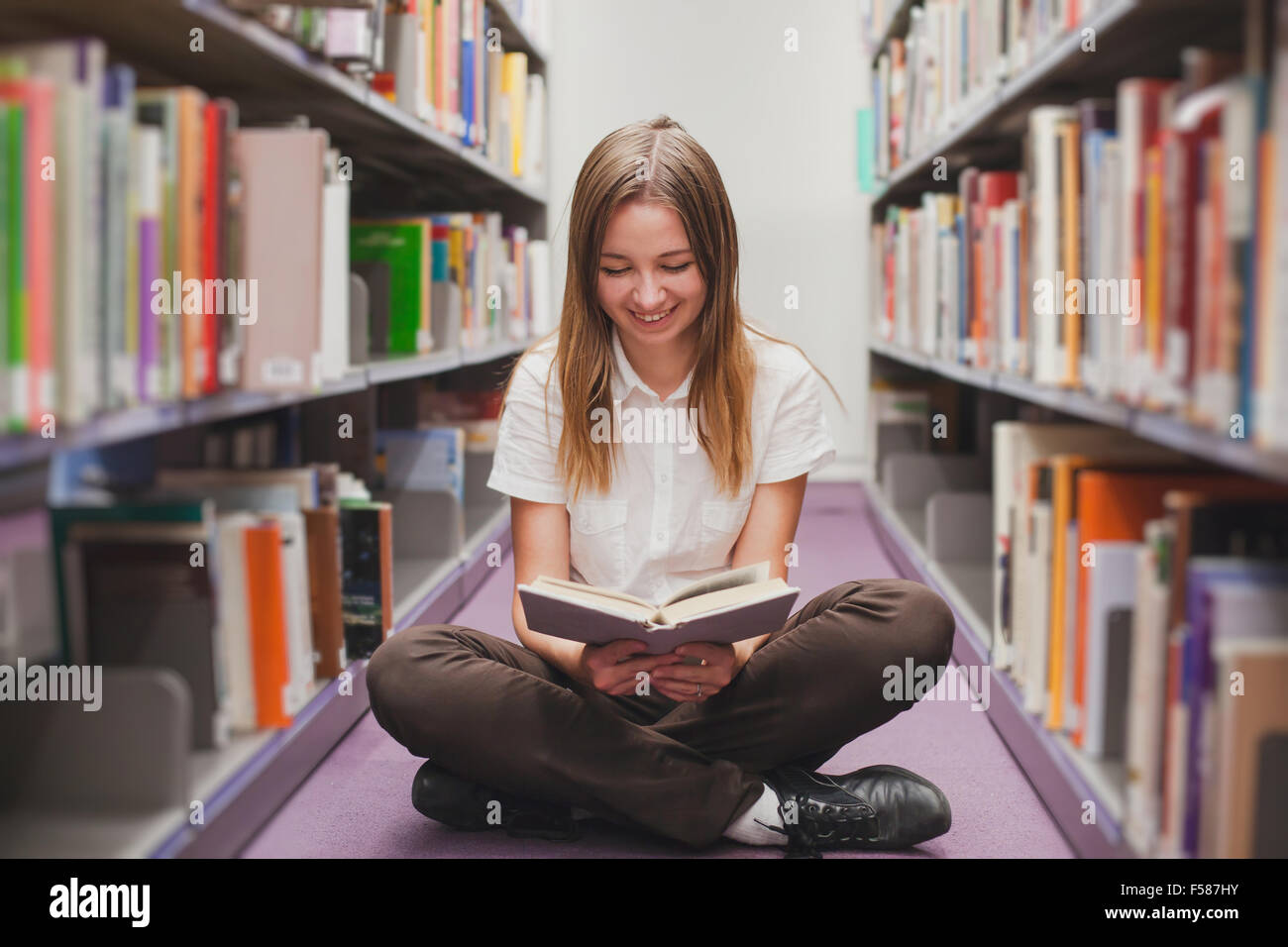 girl reading in the library, smiling happy student - Stock Image
