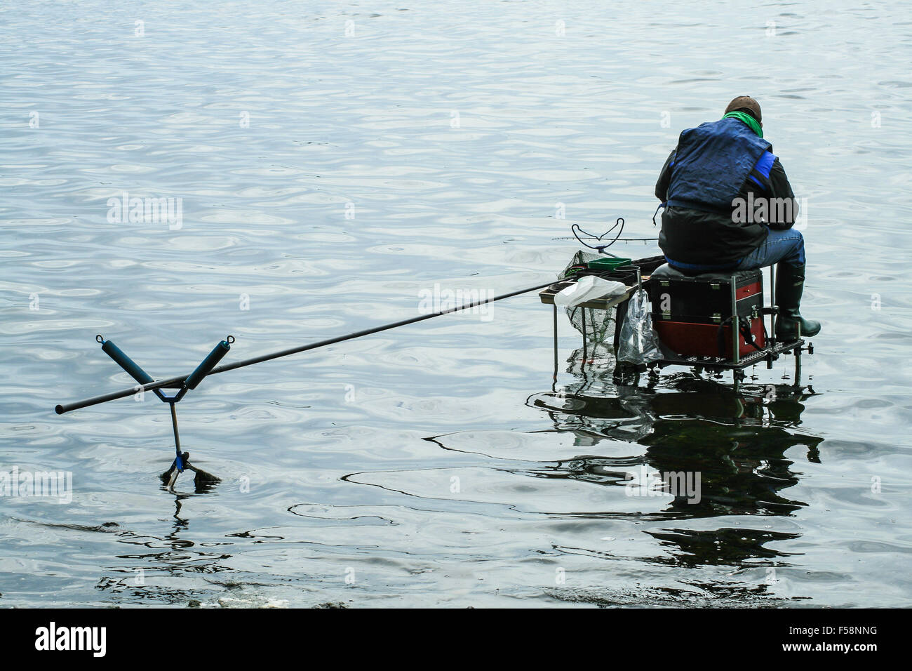 A Coarse Angling Fisherman sits on a platform over a loch - Stock Image