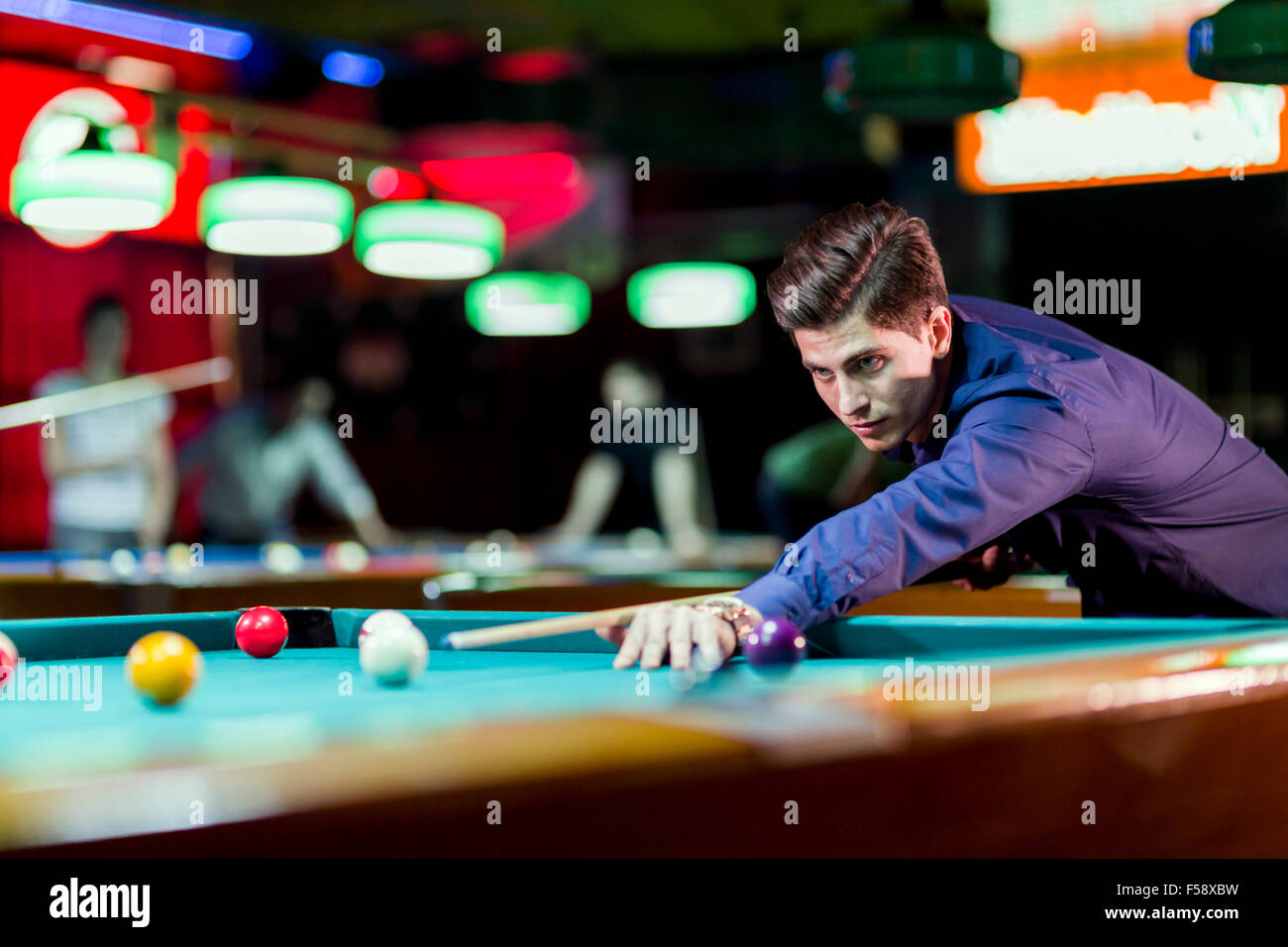 Young handsome man leaning over the table while playing snooker - Stock Image