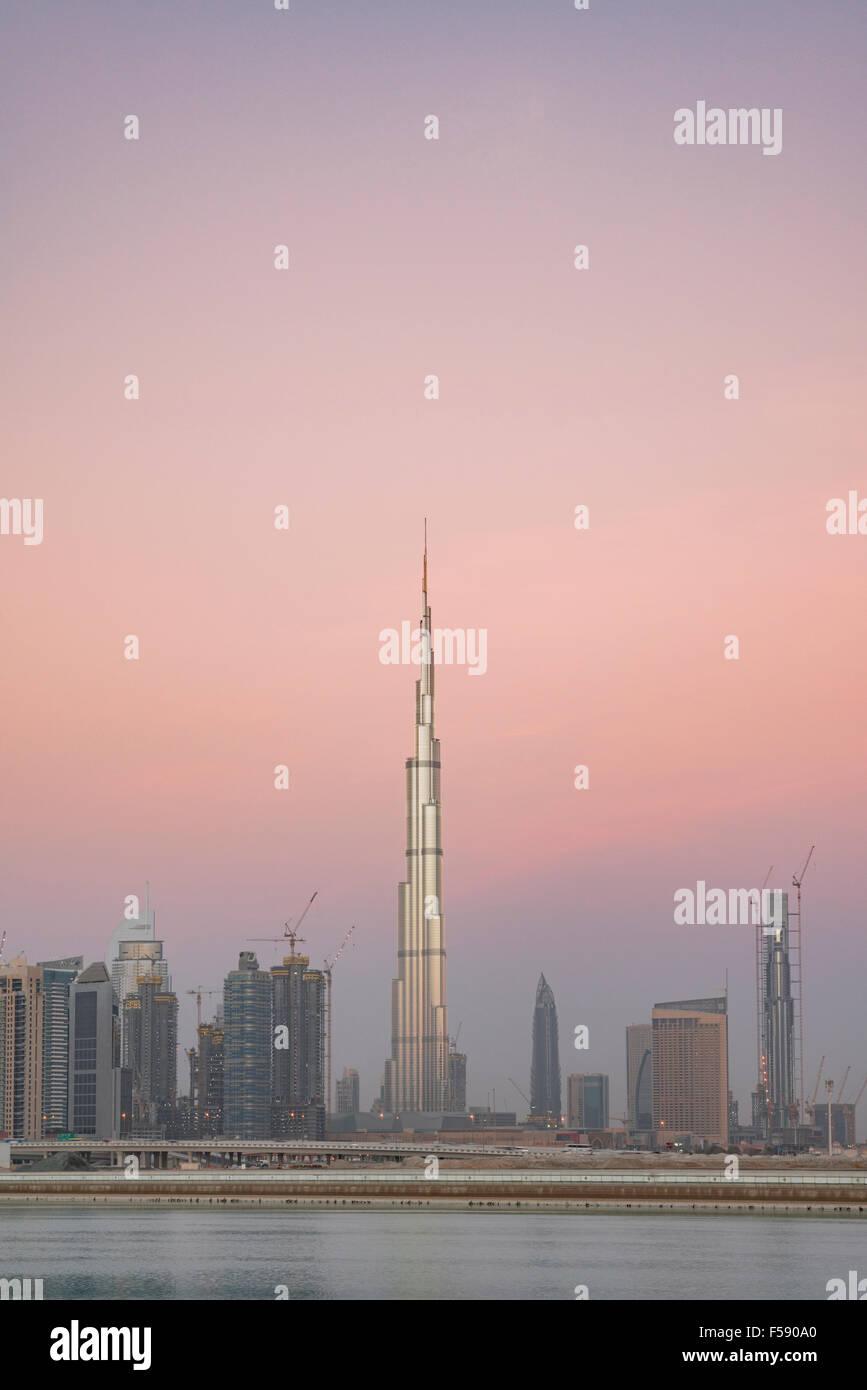 Skyline of skyscrapers and Burj Khalifa tower before sunrise in Dubai United Arab Emirates - Stock Image
