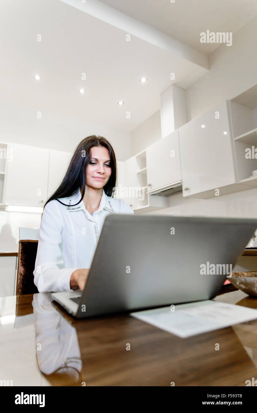 Beautiful brunette working on a laptop in her nice home - Stock Image