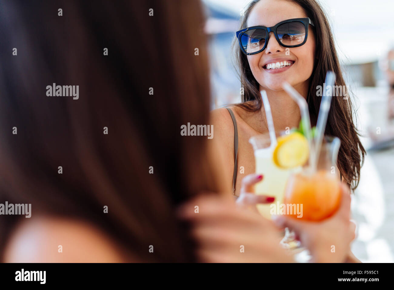 Cheerful female friends drinking cocktails in summer and smiling - Stock Image