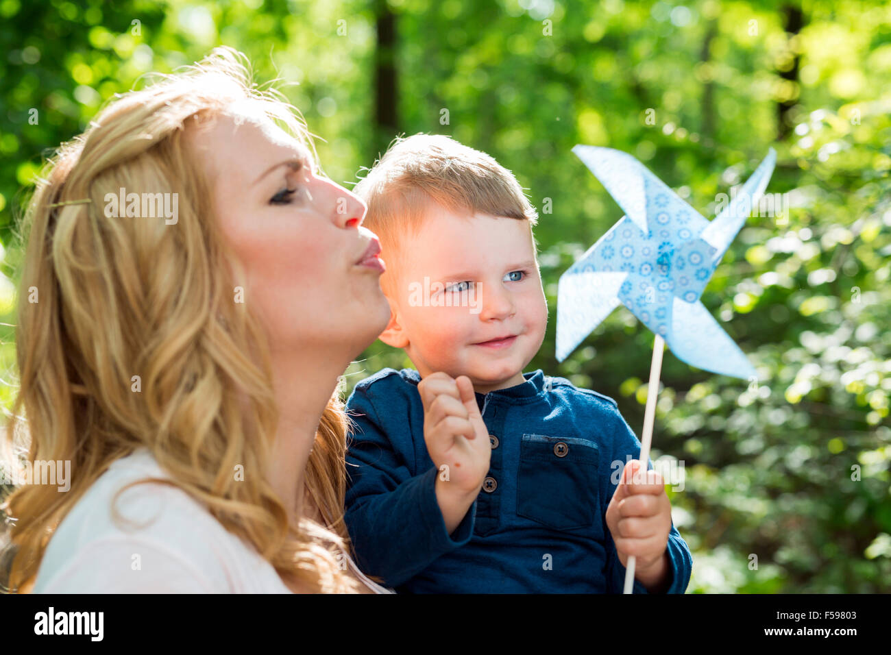 Beautiful women is blowing a paper windmill with her little son - Stock Image