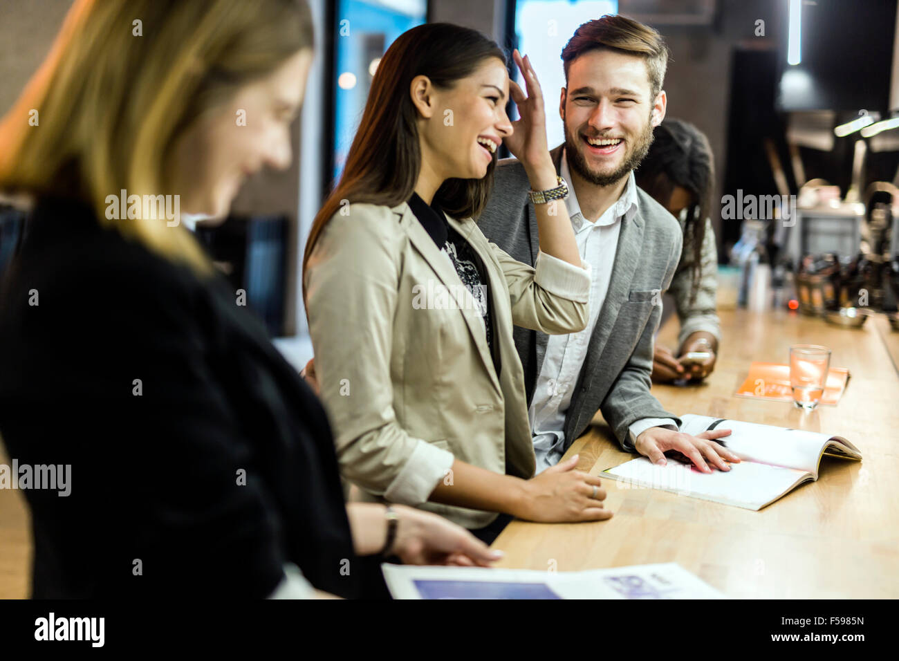 Friends at the counter of a bar after work having fun and smiling - Stock Image