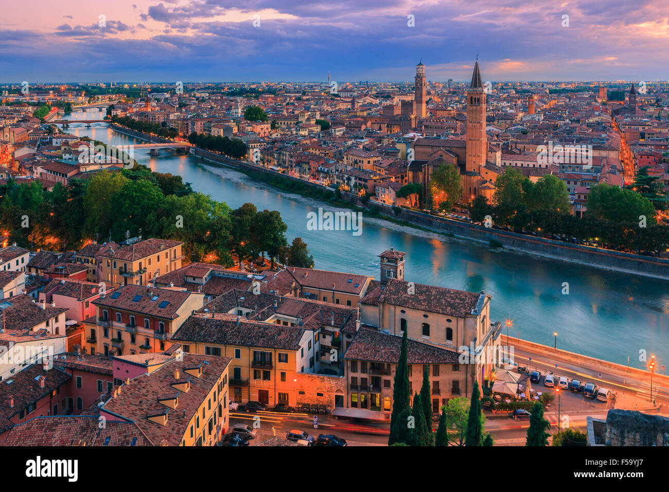 Santa Anastasia church and Torre dei Lamberti at dusk along the Adige river in Verona, Italy. Taken from piazzale - Stock Image
