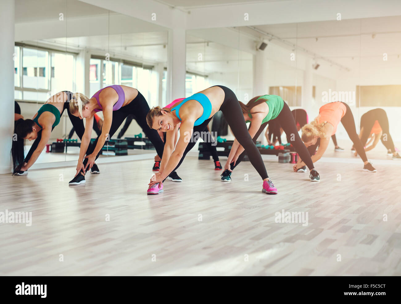 Group of women in colorful cloths in a gym doing aerobics or warming up with gymnastics and stretching exercises - Stock Image