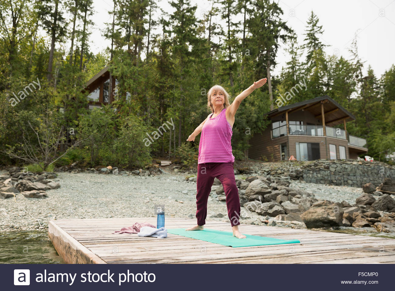 Mature woman practicing warrior 2 yoga pose dock - Stock Image