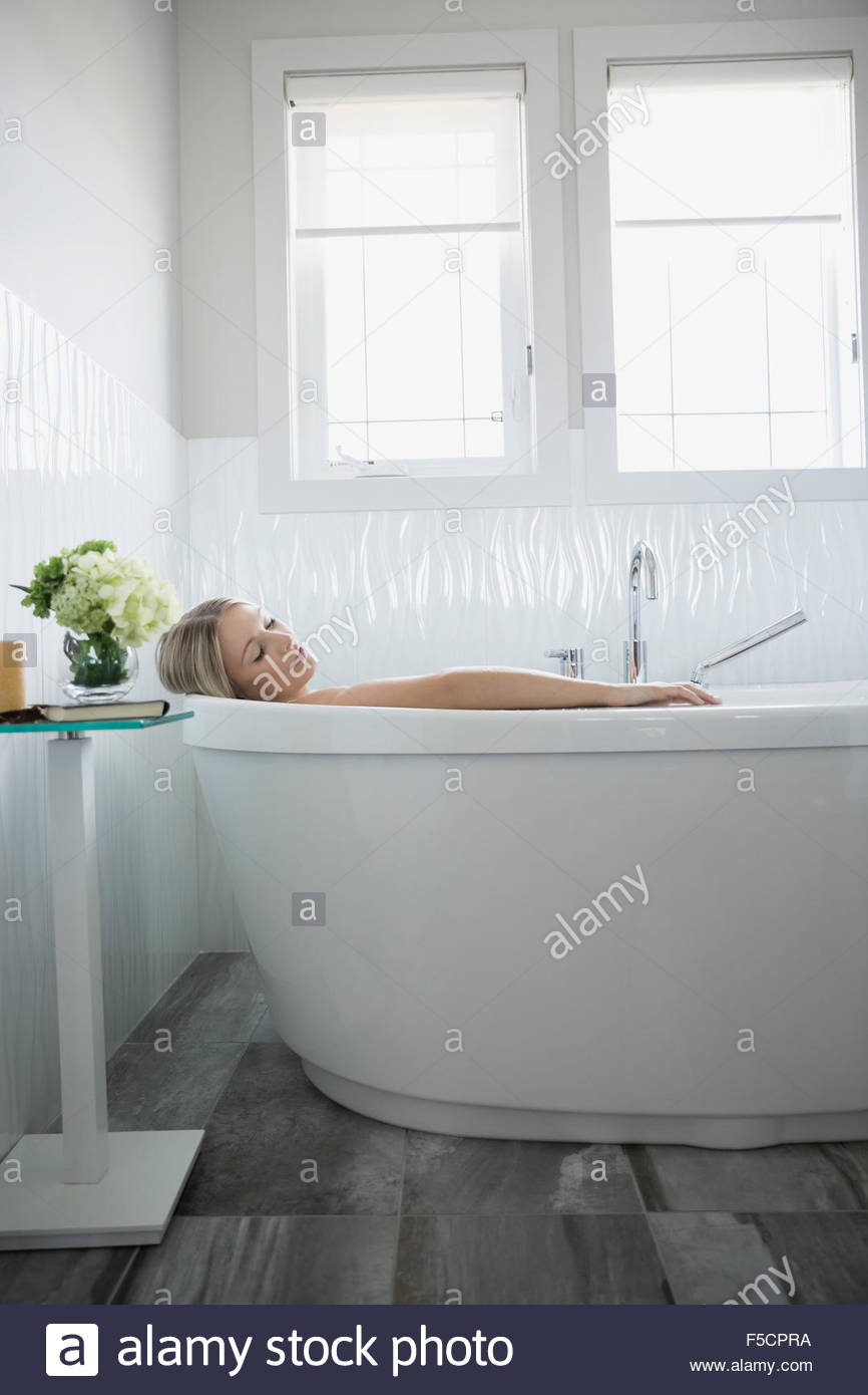 Woman relaxing in bathtub with eyes closed - Stock Image