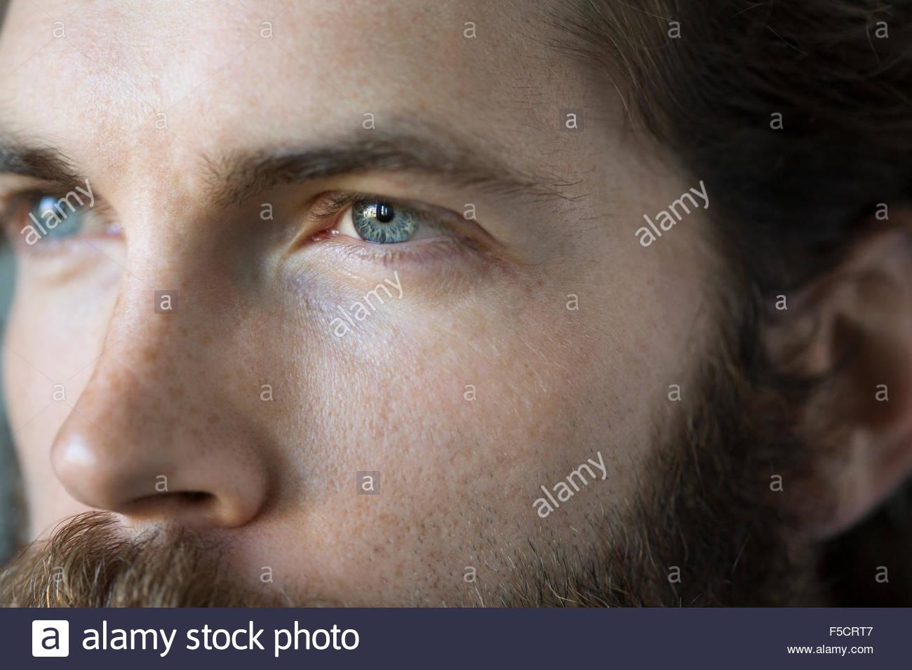 Full frame close of pensive man blue eyes - Stock Image