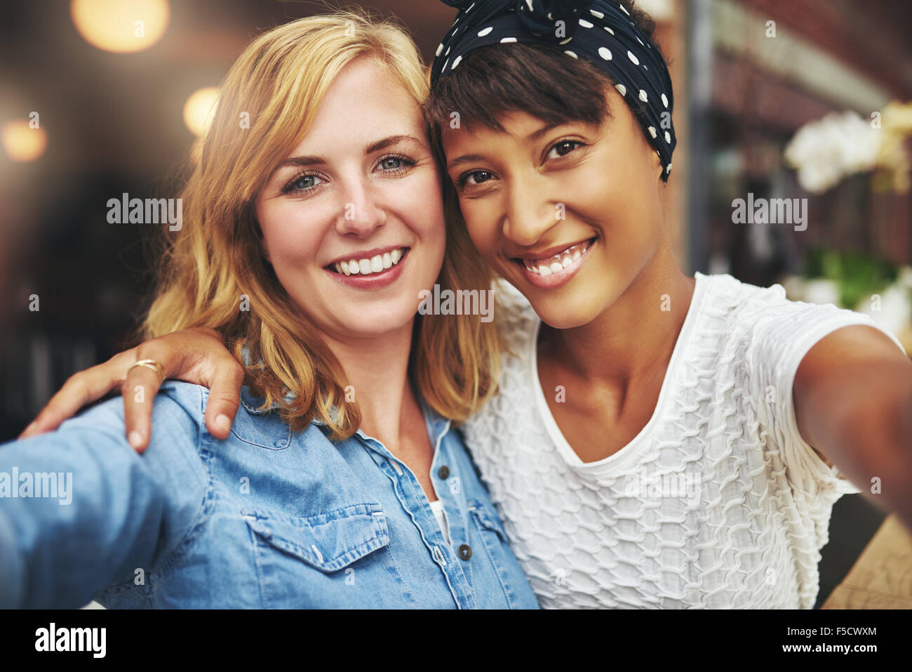 Two young women best friends sitting arm in arm with their faces close together smiling at the camera, multiethnic - Stock Image