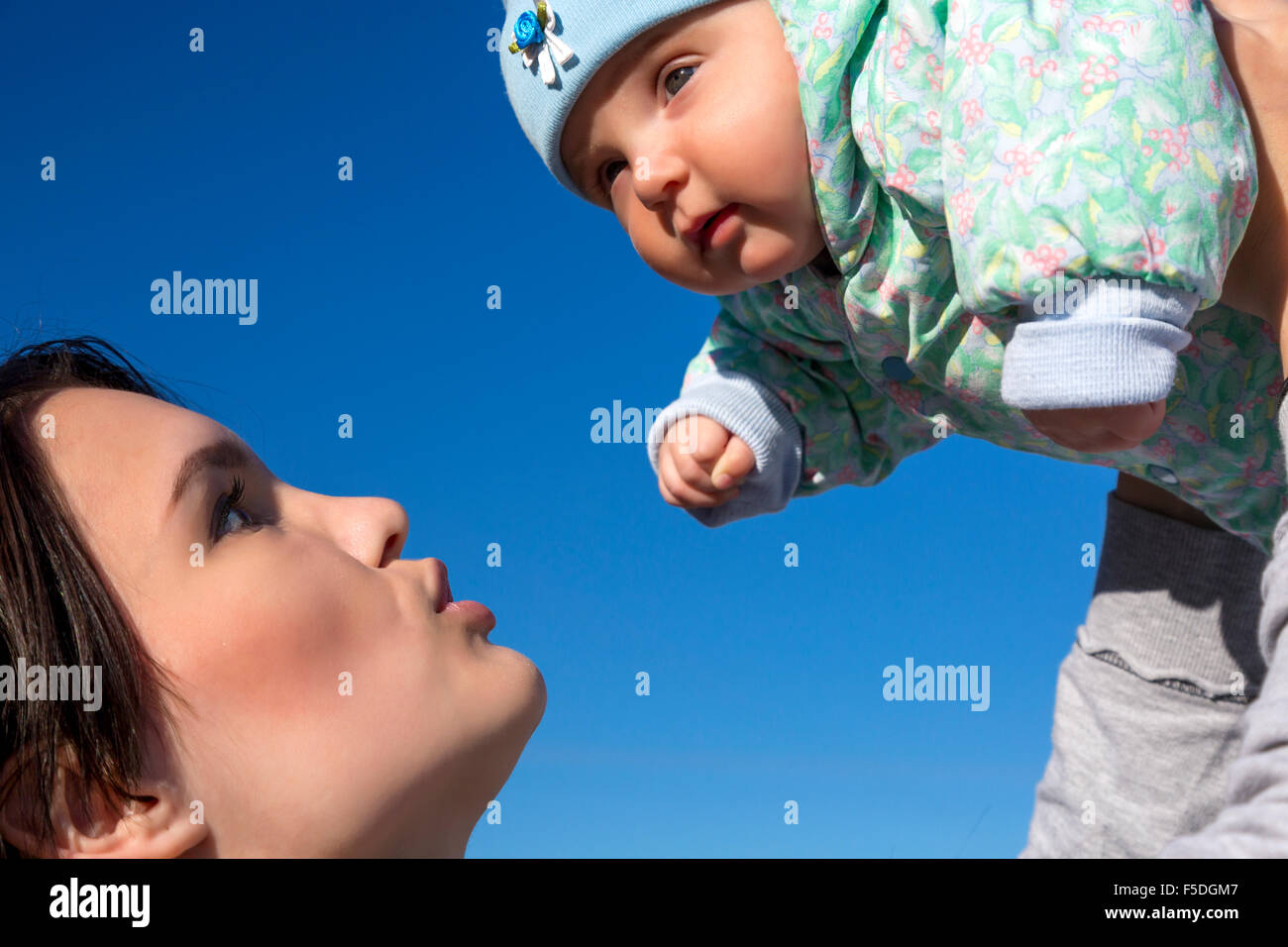 Mother and baby on blue sky background - Stock Image