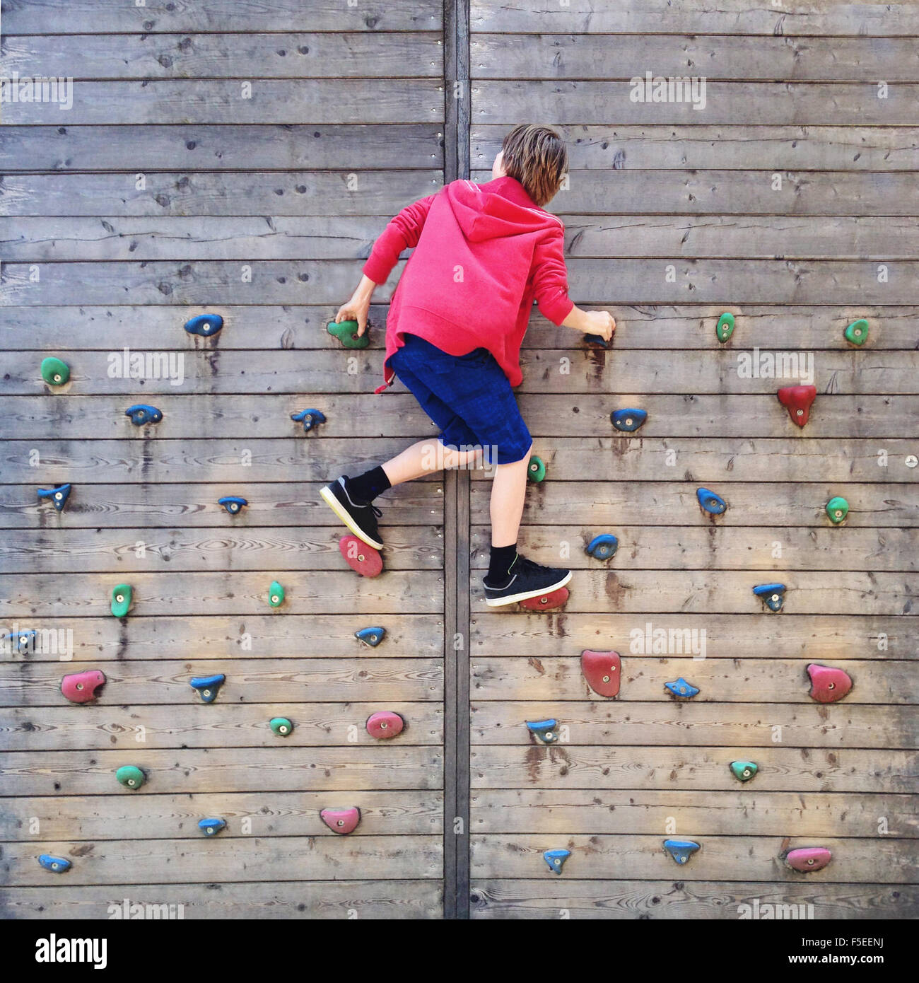 Boy climbing on climbing wall - Stock Image