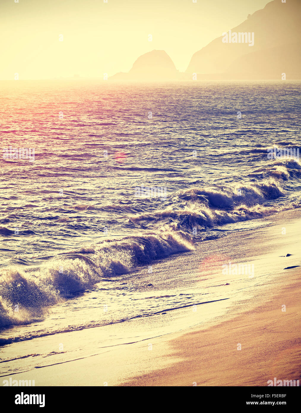 Vintage filtered beach at sunset with flare effect, California, USA. - Stock Image