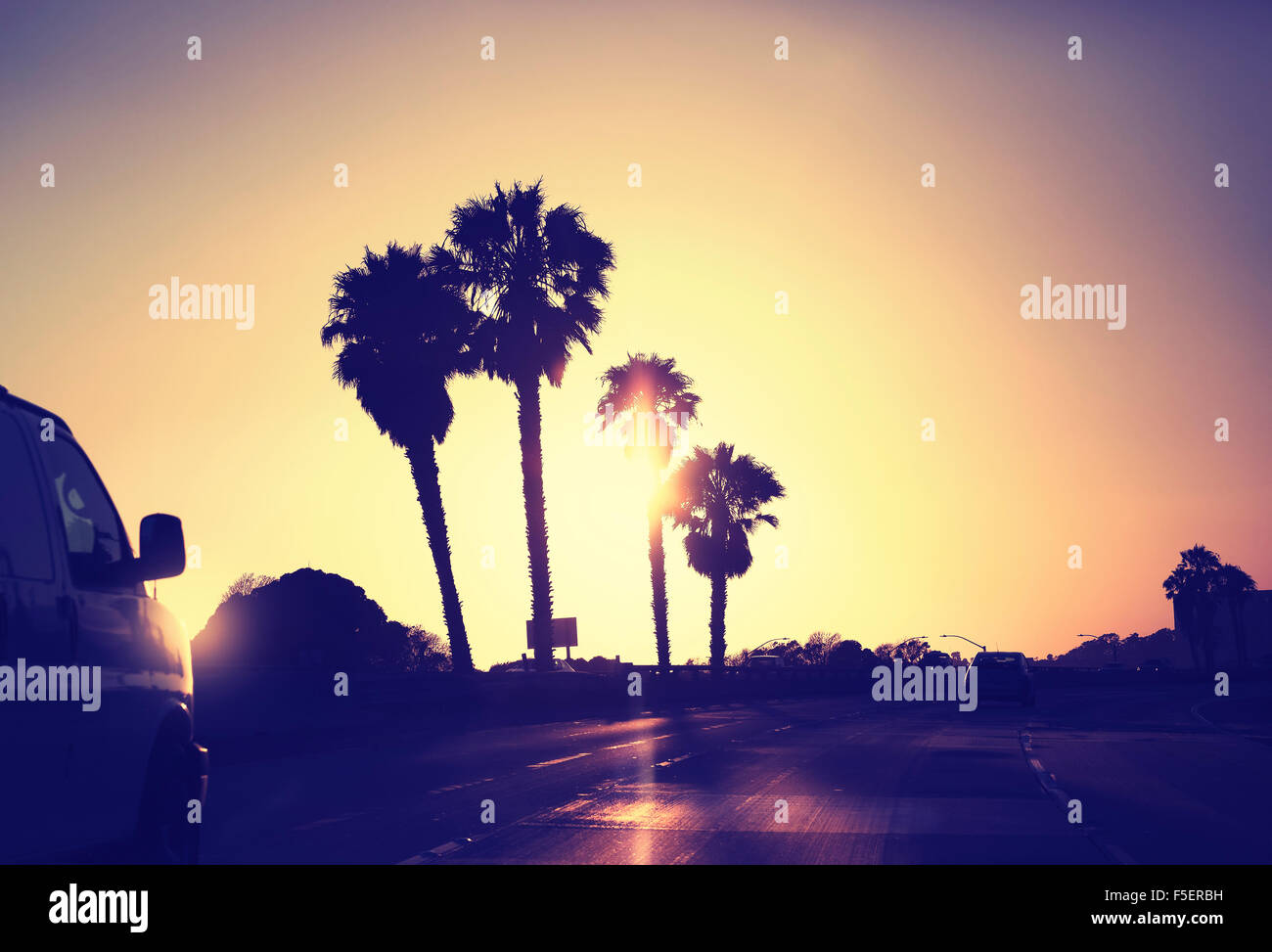 Vintage stylized picture of road against sunset, California, USA. - Stock Image