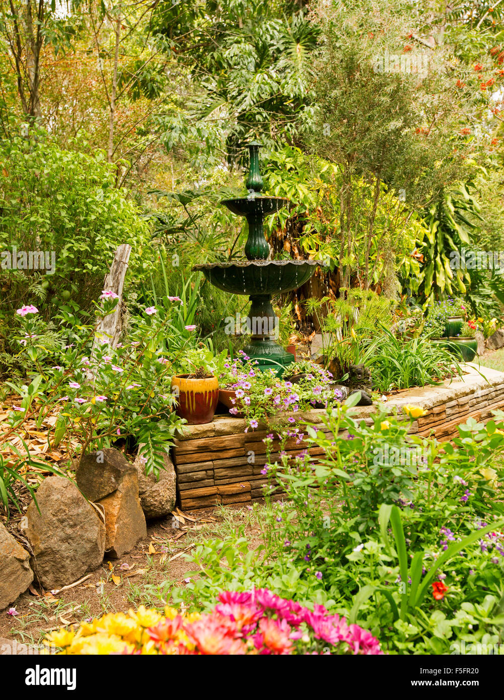 Decorative Garden Feature With Low Stone Wall, Ornate Fountain U0026 Plants In  Containers, Hemmed By Shrubs, Climbers U0026 Tall Trees