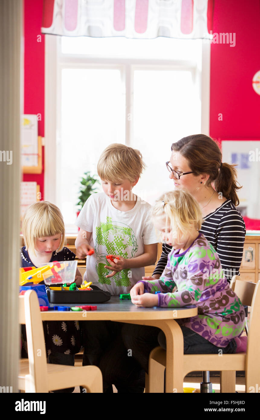 Sweden, Children playing with teacher in kindergarten Stock Photo