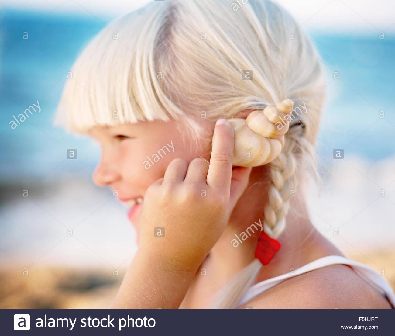 Greece, Crete, Girl (6-7) holding seashell close to ear - Stock Image