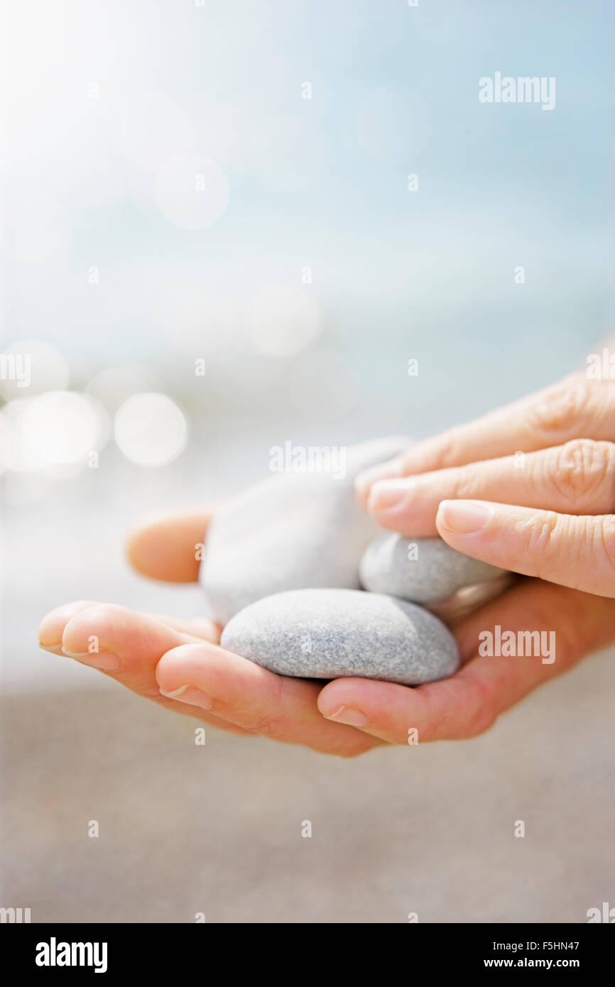 Estonia, Female hands holding white pebbles - Stock Image