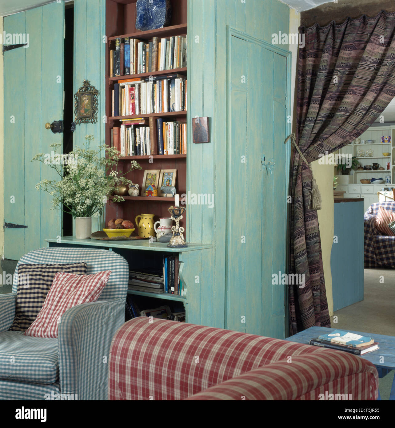 Checked armchair and sofa in a cottage living room with pale turquoise painted paneling and fitted bookcase & Checked armchair and sofa in a cottage living room with pale Stock ...