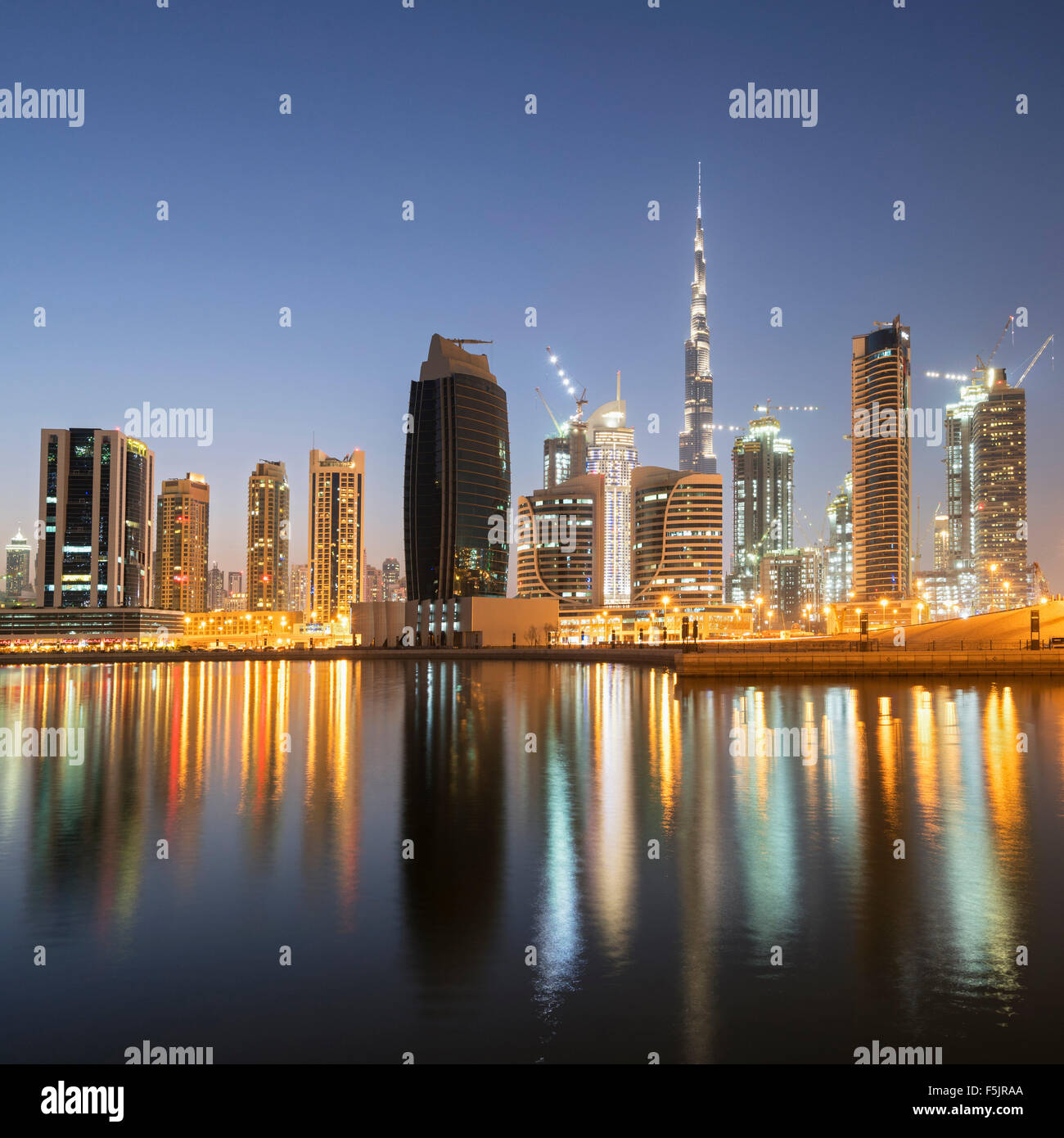 Skyline of towers reflected in the Creek at dusk in Business Bay  in Dubai United Arab Emirates - Stock Image