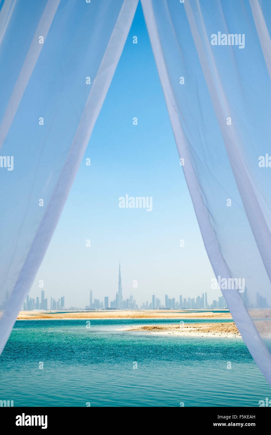 Skyline of Dubai from The Island Lebanon beach resort on a man made island, part of The World off Dubai, United - Stock Image