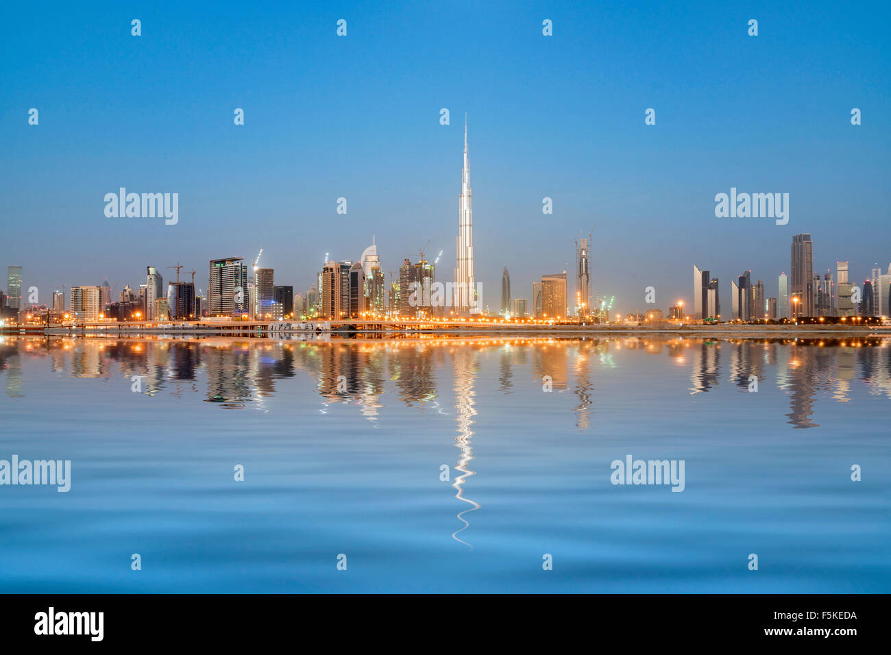 Skyline of towers reflected in the Creek at dawn in Business Bay  in Dubai United Arab Emirates - Stock Image