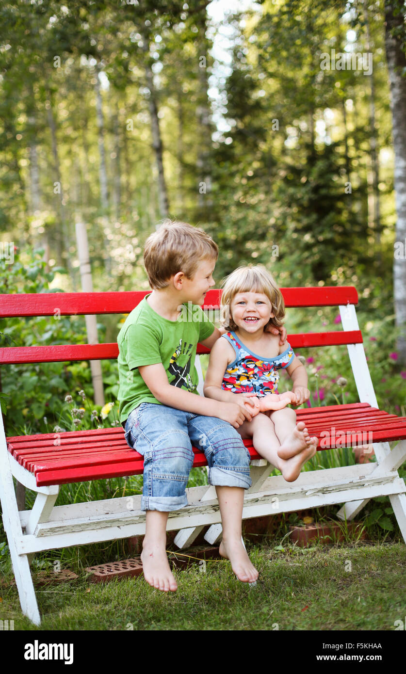 Sweden, Narke, Hallsberg, Boy (4-5) and girl (2-3) sitting on bench - Stock Image