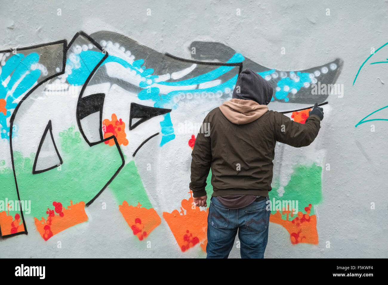 Graffiti artist spray painting part of former berlin wall mauerpark prenzlauer berg berlin germany