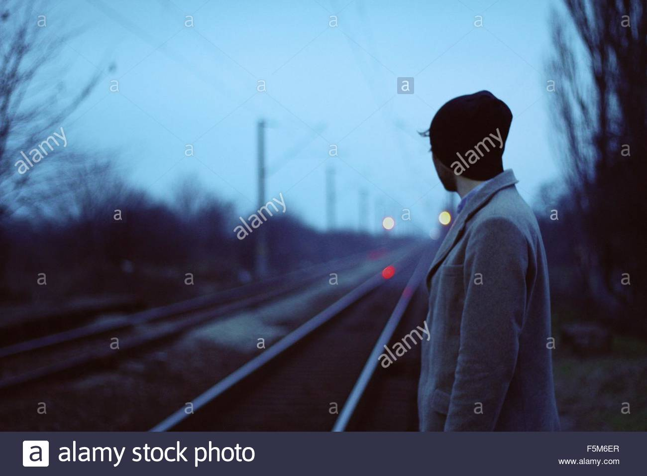 Young man looking out railway lines at dusk - Stock Image