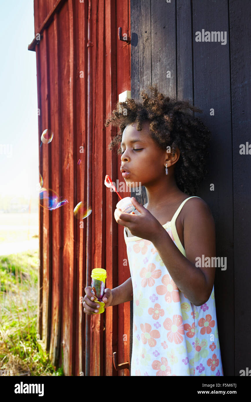 Sweden, Vastra Gotaland, Gullspang, Runnas, Girl (6-7) blowing soap bubbles - Stock Image