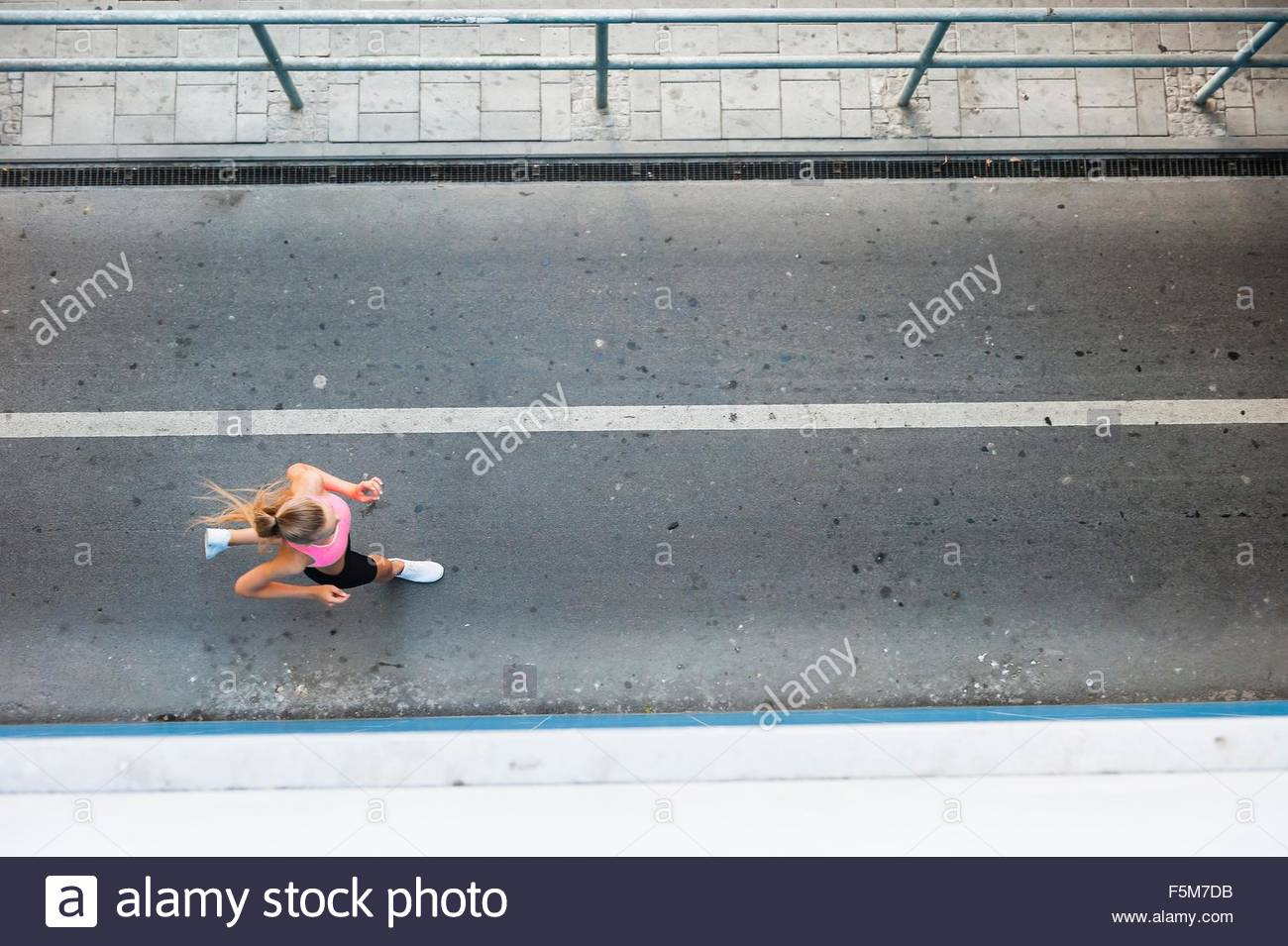 Overhead view of young female runner running along walkway - Stock Image