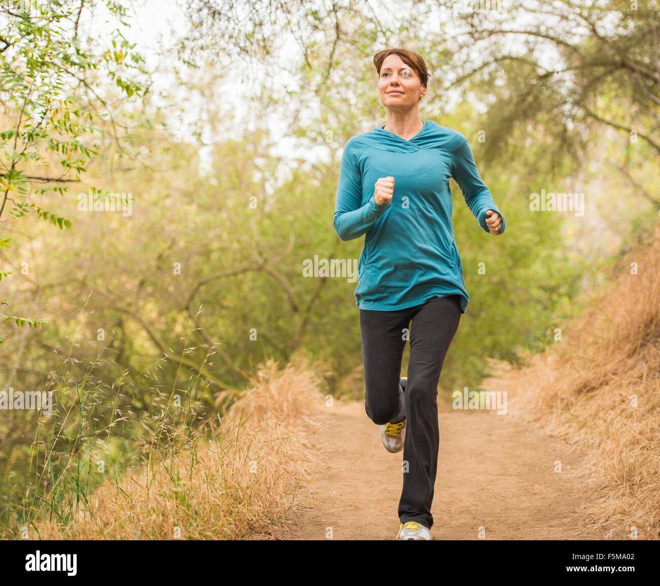 Mature woman running through forest - Stock Image