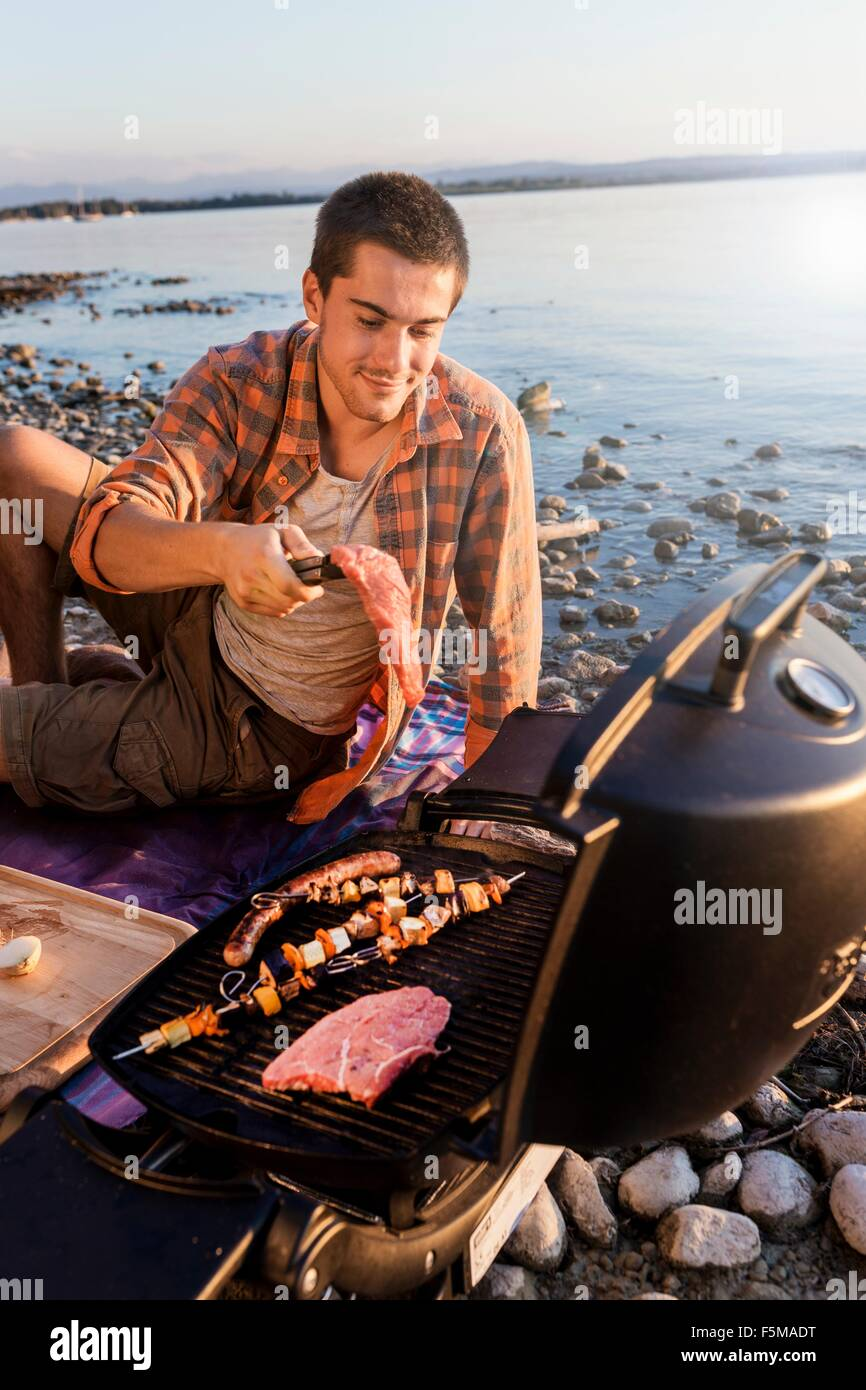 Young man sitting next to water cooking meat and kebabs on barbecue, Schondorf, Ammersee, Bavaria, Germany - Stock Image